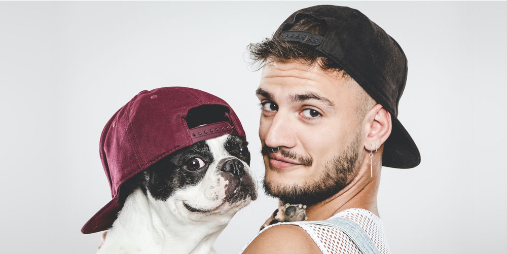 A man with dog wearing a flat billed cotton cap